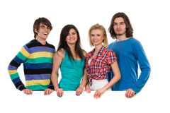 Happy group of students standing behind banner. Four young students standing behind white blank banner and smiling. Waist up studio shot isolated on white Stock Images