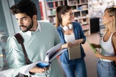 Happy group of friends studying and talking together at university royalty free stock images