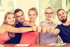 Happy group of students with thumbs up. Education, friendship, success and teenage concept. Team of friends college students giving thumb up gesture of approval Royalty Free Stock Images