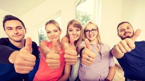 Happy group of students with thumbs up Royalty Free Stock Photos