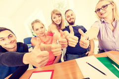 Happy group of students with thumbs up. Education, friendship, success and teenage concept. Team of friends college students giving thumb up gesture of approval Royalty Free Stock Photos