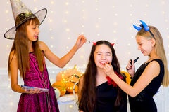 Happy group of teenagers in costumes preparing for Halloween. Near the table with pumpkins and bottle of potion Royalty Free Stock Photography