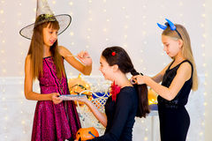 Happy group of teenagers in costumes preparing for Halloween. Near the table with pumpkins and bottle of potion Stock Photos