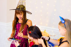 Happy group of teenagers in costumes preparing for Halloween. Near the table with pumpkins and bottle of potion Stock Photography