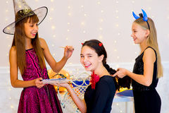 Happy group of teenagers in costumes preparing for Halloween. Near the table with pumpkins and bottle of potion Royalty Free Stock Images