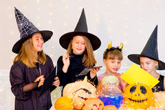 Happy group of teenagers in costumes preparing for Halloween. Playing around the table with pumpkins and bottle of potion Stock Photography