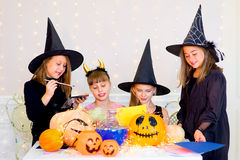 Happy group of teenagers in costumes preparing for Halloween. Playing around the table with pumpkins and bottle of potion Stock Photo