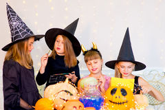 Happy group of teenagers in costumes preparing for Halloween. Playing around the table with pumpkins and bottle of potion Royalty Free Stock Images