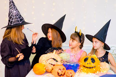 Happy group of teenagers in costumes preparing for Halloween. Playing around the table with pumpkins and bottle of potion Stock Images