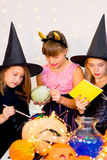 Happy group of teenagers in costumes preparing for Halloween. Playing around the table with pumpkins and bottle of potion Royalty Free Stock Photo