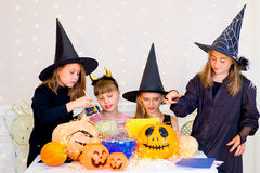 Happy group of teenagers in costumes preparing for Halloween. Playing around the table with pumpkins and bottle of potion Royalty Free Stock Photos