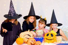 Happy group of teenagers in costumes preparing for Halloween. Playing around the table with pumpkins and bottle of potion Royalty Free Stock Image