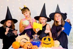Happy group of teenagers in costumes preparing for Halloween. Playing around the table with pumpkins and bottle of potion Stock Image