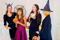 Happy group of teenagers dance in Halloween costumes Stock Photos