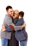 Happy group of three people hugging Stock Image