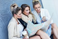 Happy group of tourists sitting outside with map in autumn season stock photos