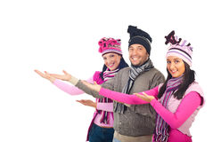 Happy group in winter clothes welcoming. Happy group of three friends  wearing colorful winter knitted clothes standing in a row with welcome hands gesture to Royalty Free Stock Photos