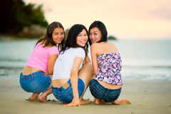 Happy group of woman at the sunset beach. Group of happy asian woman friends squatting by the sunset beach Stock Photo
