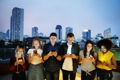 Happy group of young adults using smartphones. In the cityscape stock photos