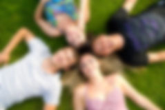 Happy group of young friends lying one the grass Royalty Free Stock Photography