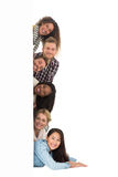 Happy group of young friends peeking from behind a wall Stock Images
