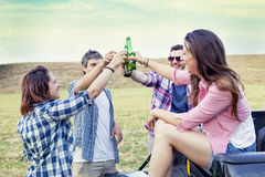 Happy group of young friends toasting with beer. Outdoors at sunset stock image