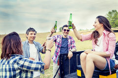 Happy group of young friends toasting with beer. Outdoors at sunset royalty free stock image