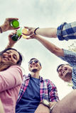 Happy group of young friends toasting with beer. Outdoors at sunset royalty free stock photo