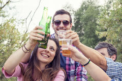 Happy group of young friends toasting with beer. Outdoors at sunset stock photos
