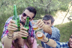 Happy group of young friends toasting with beer. Outdoors at sunset stock photography