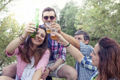Happy group of young friends toasting with beer. Outdoors at sunset royalty free stock images