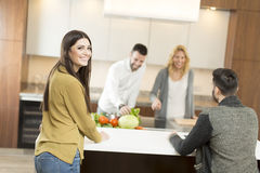 Happy group of young  men and women in modern kitchen Royalty Free Stock Image