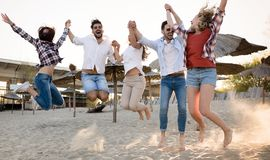 Happy group of young people having fun at beach Stock Photos