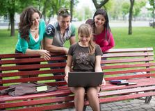 Happy group of young students sitting Royalty Free Stock Images