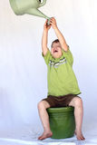 Happy Growing Child. A young boy reaches to a watering can while sitting on a gardening pot laughing Royalty Free Stock Photo
