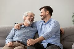 Happy grown son sit on couch talk with senior dad royalty free stock image