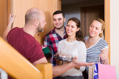 Happy guests in doorway. Cheerful smiling guests with cake and presents standing in doorway Royalty Free Stock Photography