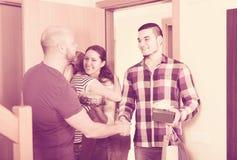 Happy guests in doorway. Positive guests with presents and cake standing in doorway. Focus on man Stock Photo
