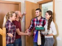 Happy guests in doorway. Positive smiling guests with cake and presents standing in doorway Stock Photo