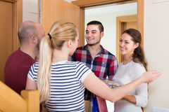 Happy guests in doorway Stock Photography
