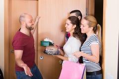 Happy guests in doorway. Happy smiling cheerful guests with gifts in hands standing in doorway. Focus on girl Stock Photography