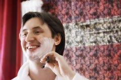 Happy guy in bathrobe shaving Royalty Free Stock Photo