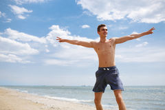 A happy guy at the beach. A smiling teenager at the sea background. Tropical vacation at the ocean concept. Copy space. A happy, smiling young guy in dark blue Stock Photography