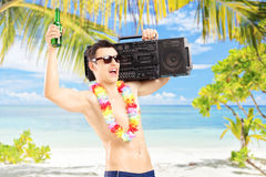 Happy guy with beer and boombox on his shoulder gesturing happin. Ess on a tropical beach Stock Photography