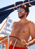 Happy guy behind wheel of sailboat Royalty Free Stock Photo
