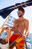 Happy guy behind wheel of sailboat Royalty Free Stock Photo
