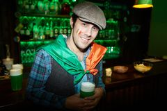 Young man in pub. Happy guy in cap leaning against bar counter in pub and looking at camera Royalty Free Stock Photo