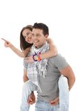 Happy guy carrying girlfriend on back. Girl pointing, laughing, wearing casual summer clothes, isolated on white stock photography