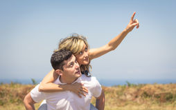 Happy guy carrying his girlfriend on back outdoors Stock Image