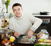 Happy guy cooking trout fish with onion Royalty Free Stock Photo